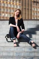 jonge modieuze vrouw zittend op de trappen foto