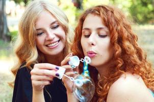 twee vriendinnen zeepbellen blazen foto