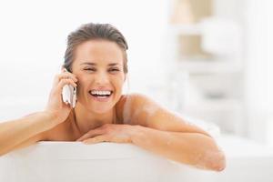 glimlachende jonge vrouw die mobiele telefoon in badkuip spreekt foto