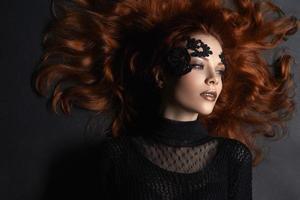 mooi roodharig meisje kant make-up in het donker foto