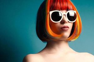 mooie vrouw draagt kleurrijke pruik en witte zonnebril tegen foto