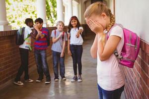 triest schoolmeisje met vrienden op achtergrond op school gang foto