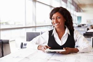 jonge vrouwelijke architect die bij haar bureau werkt, weg kijkend foto