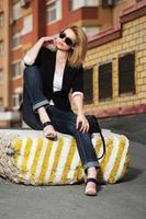 triest mooie vrouw zittend op de stoep van de stad foto