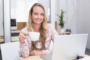 vrolijke zakenvrouw met behulp van haar notitieblok met een beker foto