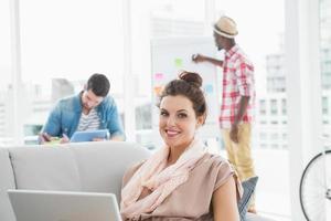 Glimlachende zakenvrouw op de bank met behulp van laptop foto