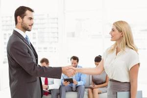zakenman handen schudden met vrouw naast mensen die wachten op interview foto