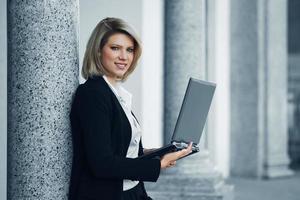 jonge zakenvrouw met behulp van laptop aan de muur foto
