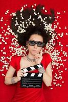 verbaasd meisje met 3D-bioscoop bril, popcorn en regisseur dakspaan