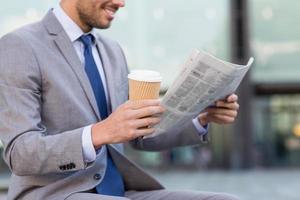 sluit omhoog van de glimlachende krant van de zakenmanlezing foto
