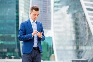 knappe zakenman in pak met slimme telefoon in de hand foto