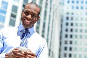 glimlachende mannelijke uitvoerende macht die zijn mobiele telefoon met behulp van foto