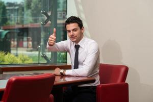 lachende zakenman met duim omhoog foto