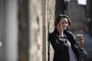 moderne zakenvrouw, praten op mobiele telefoon buiten. foto