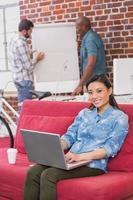 casual vrouw met laptop op de bank foto