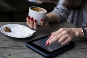de hand die van de vrouw op tablet doorbladert en koffie houdt