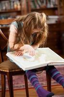 jong meisje dat door een atlas kijkt foto