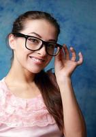 mooie glimlachende vrouw in glazen op blauwe achtergrond foto