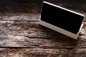 telefoon op een standaard op een houten mockup als achtergrond foto