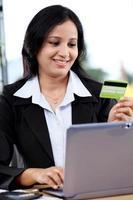 glimlachende jonge bedrijfsvrouw die online het winkelen doet foto