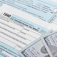 VS belasting 1040 formulier en 100 Amerikaanse dollarbiljetten foto