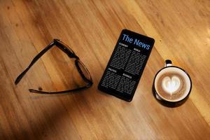 nieuws in mobiel met koffiekop en spects foto