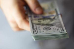 stapels van honderd dollar in de hand foto