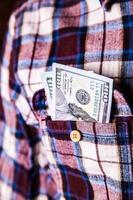 honderd Amerikaanse dollars in de zak met shirt foto