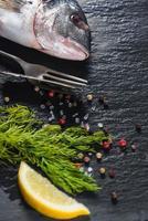 verse hele zeevis met aromatische kruiden, koken concept foto