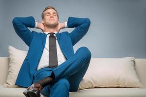 knappe zakenman ontspannen op de bank foto