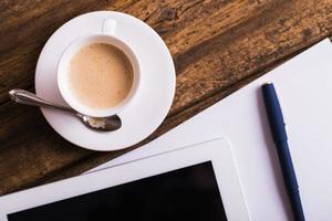 digitale tablet en koffie op oude houten achtergrond foto