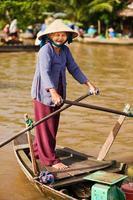 Vietnamese vrouw roeiboot in de mekong rivierdelta, vietnam foto