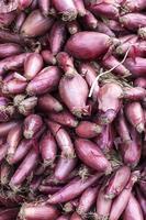 rode uien verkocht op de traditionele markt voor groenten foto