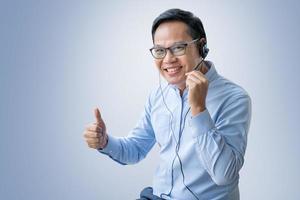 mens die op middelbare leeftijd vraag op hoofdtelefoon neemt die op blauwe achtergrond wordt geïsoleerd foto