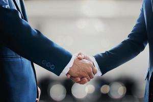 portret van twee zakenlieden handen schudden om partnerschap te vieren