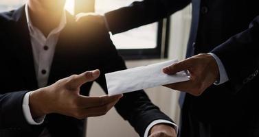 raamverlichte scène van twee zakenlieden die een envelop uitwisselen foto
