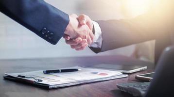 twee zakenlieden schudden elkaar de hand om een zakelijke deal te vieren