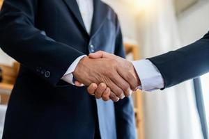 twee zakenlieden schudden elkaar de hand om een onderhandelingsovereenkomst op het werk af te sluiten