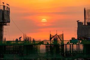 avondtijd van hoge bouwconstructieplaats, over tijd arbeider foto
