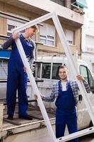 zorgvuldige werklieden die raamkozijnen van een vrachtwagen dragen foto