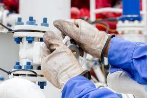 close-up handen klep openen in de petrochemische fabriek. foto
