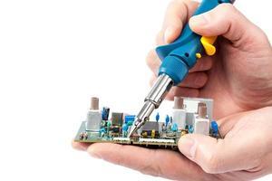 soldeerbout in de hand en elektrisch bord. foto