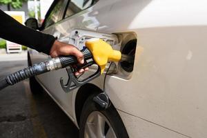 hand de auto bijvullen met brandstof, focus hand foto