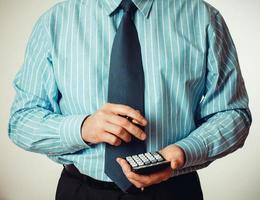 zakenman in blauw shirt met rekenmachine foto