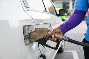 hand houden brandstofpijp om brandstof in de auto toe te voegen foto