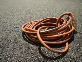 het oranje verlengsnoer op de grond op de bouwplaats foto