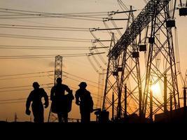 silhouet van ingenieur die blauwdrukken in een bouwterrein bekijkt foto