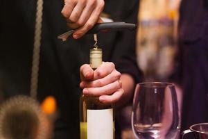 het openen van een wijnfles met kurkentrekker foto