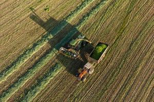 luchtfoto van oogstvelden met maaidorser en tractor foto