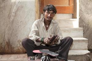 Indiase schoenpoetser in de straten van Delhi foto